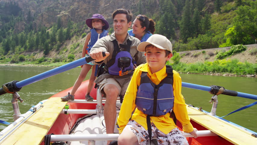 American Caucasian family rafting on Colorado River on vacation outdoors