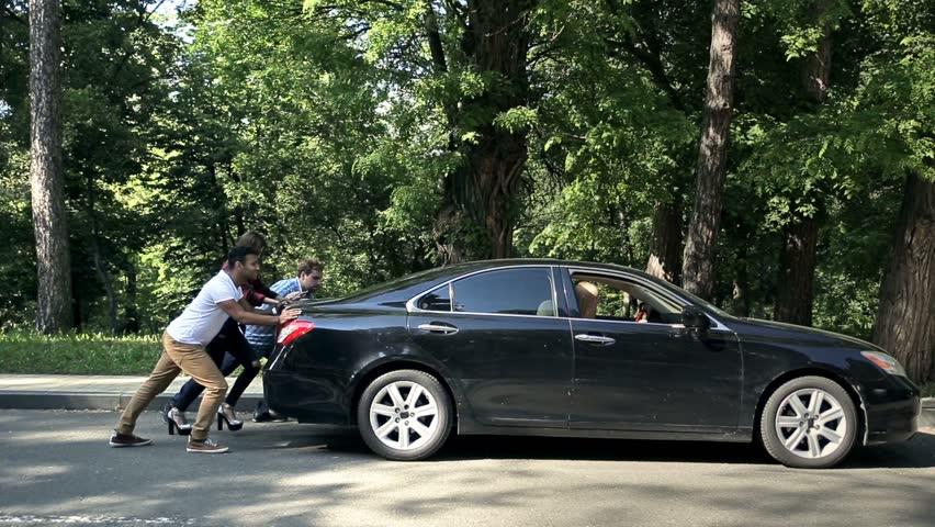 Men helping charming women to push car on road