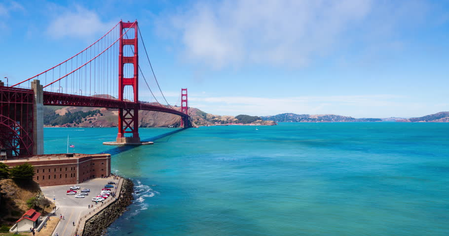 Golden Gate Bridge Time Lapse Pan Left. a time lapse panning left from Alcatraz prison to the Golden Gate Bridge in San Fransisco, California during a sunny day with the clouds and fog moving overhead