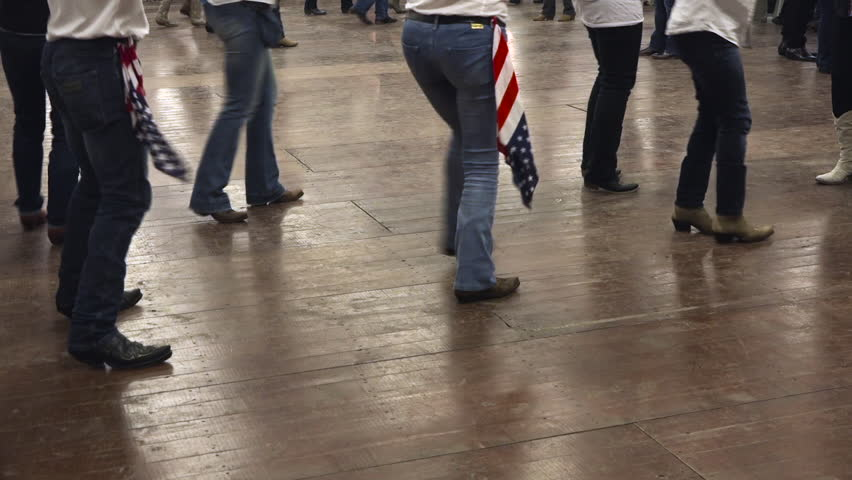 Western dancers dancing a choreography at a country festival, wearing cowboy boots, jeans and USA flag. Learning line dance. Music, traditions and fun | Shutterstock HD Video #18356263
