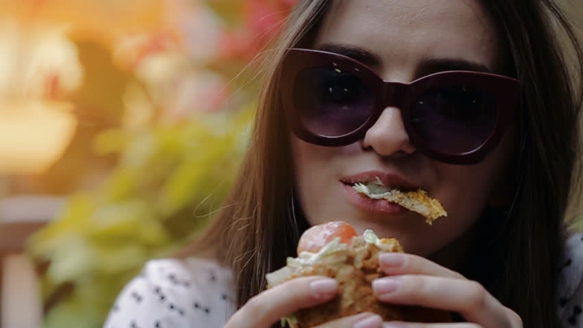 Beautiful Girl Eats Burger on the Street in Chicago. Tasty Burger . Beautiful Girl Savors Burger #18369499