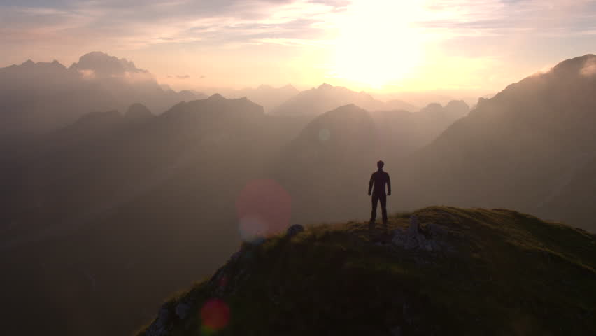 Aerial - Flyover silhouette of a man standing on top of the mountain and watching beautiful sunset over the peaks | Shutterstock HD Video #18379717