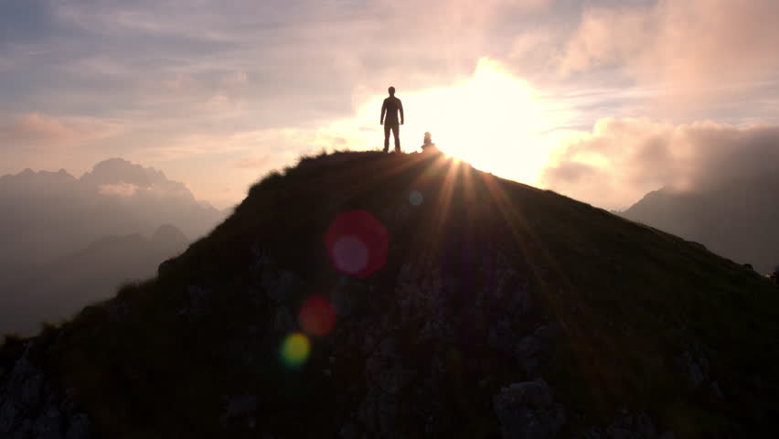 Aerial - Moving above silhouette of a man standing on top of the mountain. Man raising arms victoriously after climbing the mountain | Shutterstock HD Video #18379804