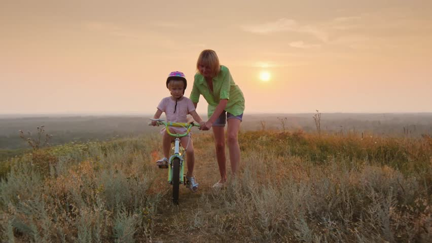 Mom teaches daughter to ride a bike. Concept - the first success. At sunset | Shutterstock HD Video #18388003