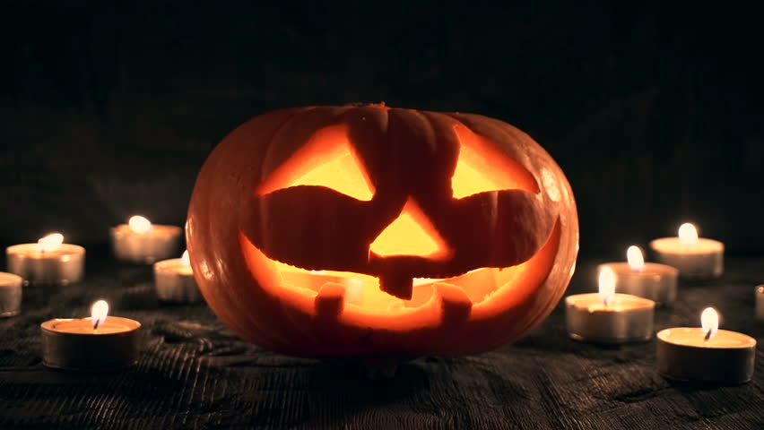 Carved Halloween pumpkin on a black background with lighted candles. 4k motion | Shutterstock HD Video #18400591