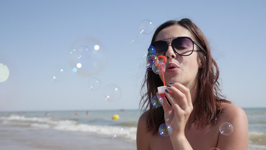 Female on ocean beach blowing soap bubbles slow-mo 1920X1080 HD video - Happy and beautiful young brunette playing with air-bubbles near sea coast slow motion lifestyle 1080p FullHD footage
