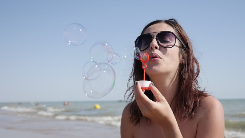 On ocean beach female blowing soap bubbles slow-mo 1920X1080 HD video - Happy and beautiful young brunette playing with air-bubbles near sea coast slow motion lifestyle 1080p FullHD footage
