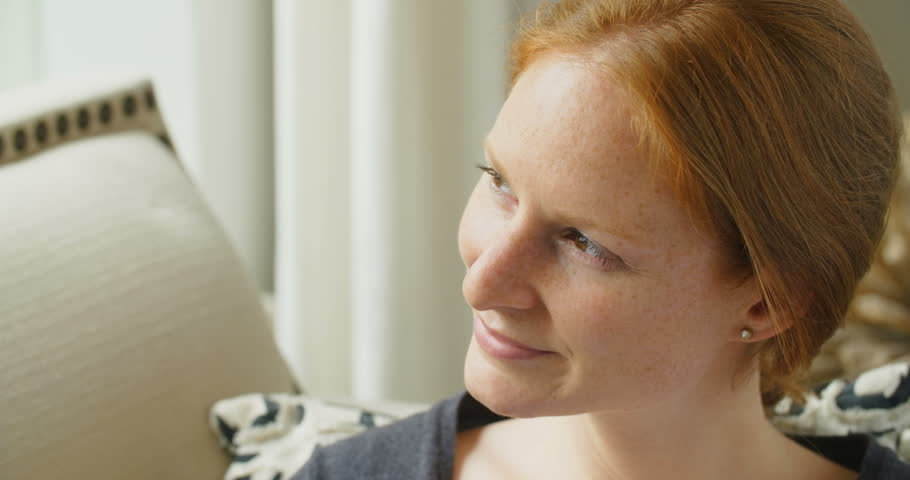 Slow motion closeup shot of a young redhead woman smiling at the camera. | Shutterstock HD Video #18418405