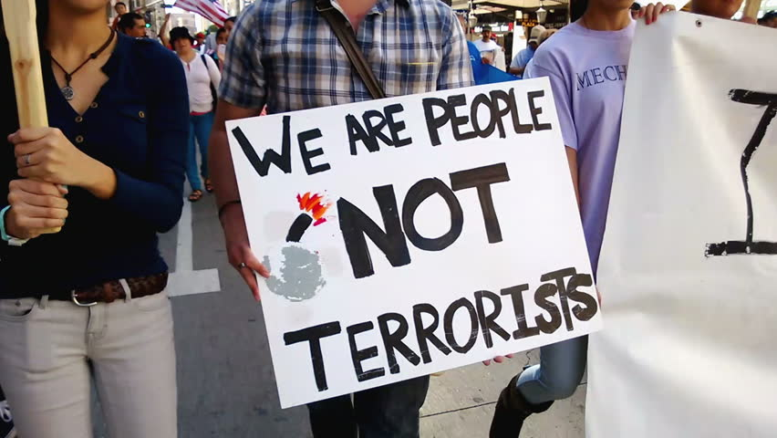 """""""We Are People Not Terrorists"""" Rally Sign. A white picket sign that reads, """"We Are People, Not Terrorists"""" is held up during an immigration rally in downtown Los Angeles on September 22, 2013."""