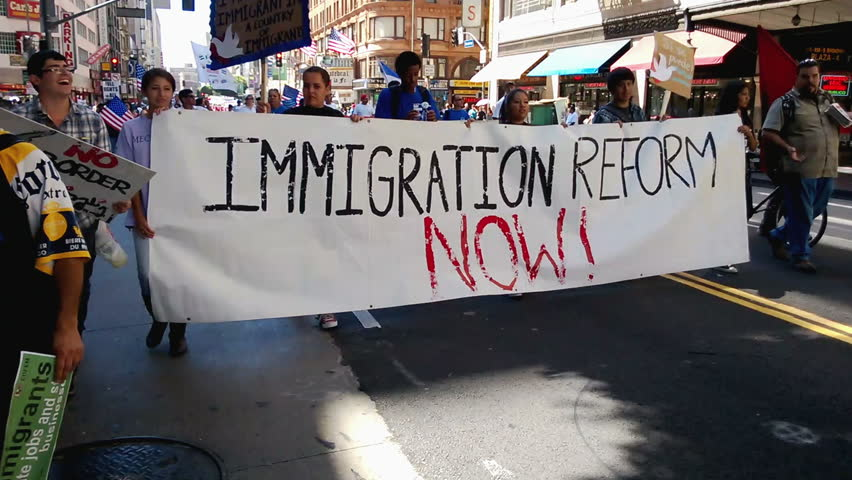 """Immigration Reform Banner. A large white picket banner that reads, """"Immigration Reform Now!"""" is held up and carried by multiple people during an immigration rally in Los Angeles on September 22, 2013."""