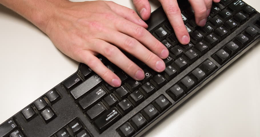Large white masculine looking hands type words on black PC computer keyboard then hit enter key and continue typing.