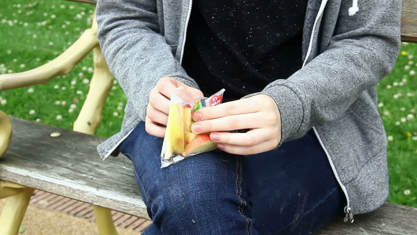 Young adult or late teens woman seated in park opening a pack of Tesco pre-sliced apple for a snack. Model released, no property release for pack of sliced apple. | Shutterstock HD Video #18439786