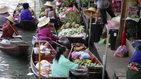 RATCHABURI, THAILAND - APRIL 27, 2014 : Unidentified people on food boats at Damnoen Saduak floating market . Damnoen Saduak is a very popular tourist attraction near Bangkok in Thailand.