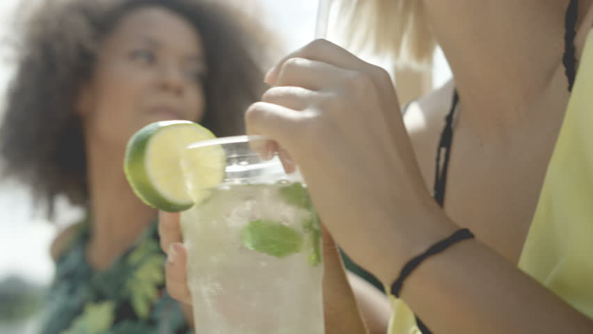 Close up of woman enjoying tropical mojito cocktail decorated with fresh lemon. Two beautiful friends having fun during vacation. #18461947