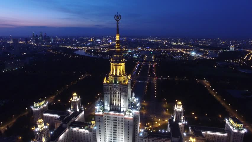 Beautiful evening shot of MSU Moscow State University. Unique night Aerial drone footage. Flight near spire and star, high altitude. Illumination. Stalin skyscraper.