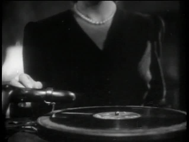 Close-up of hands placing needle on record, 1940s