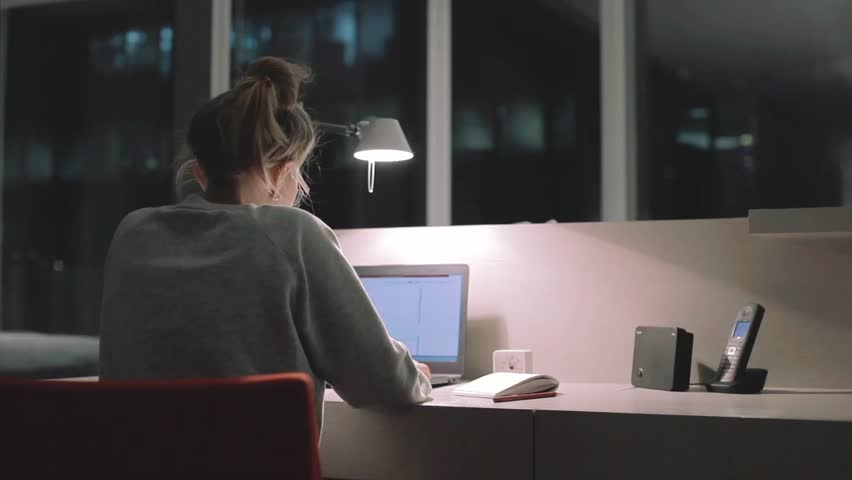 Young concentrated woman, sitting in her room or office with french windows in the dark at the lamp.Studies late at night.Staying up late. Overworking. Working late on laptop.     | Shutterstock HD Video #18499183