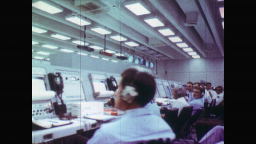 UNITED STATES 1960s:View of People Working at Computer Station in their Headphones. Men Sat Waiting for Space Rocket to Take Off. NASA Mission Control Room | Shutterstock HD Video #18554417