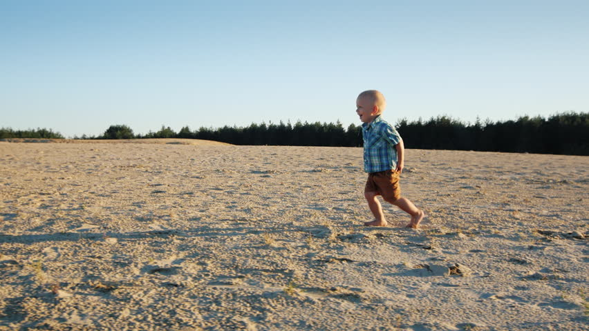 Steadicam shot: Cool kid running across the sand, rejoices. Slow-motion video   Shutterstock HD Video #18556670