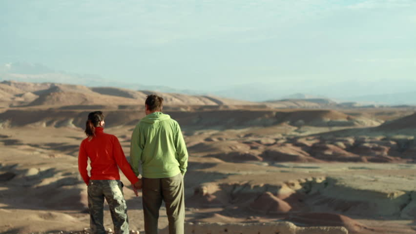 Couple in the mountains holding hands and looking at landscape  | Shutterstock HD Video #1855750
