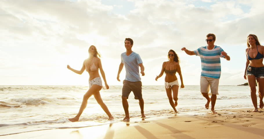 Group of friends having fun running down the beach at sunset #18569282