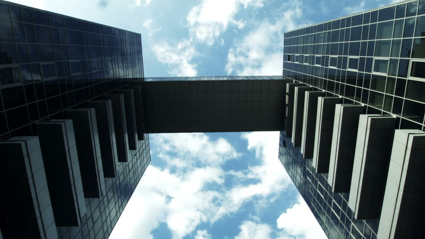 Timelapse of looking up from below at a sky bridge between two skyscrapers allowing covered access against a cloudy blue sky #18577493