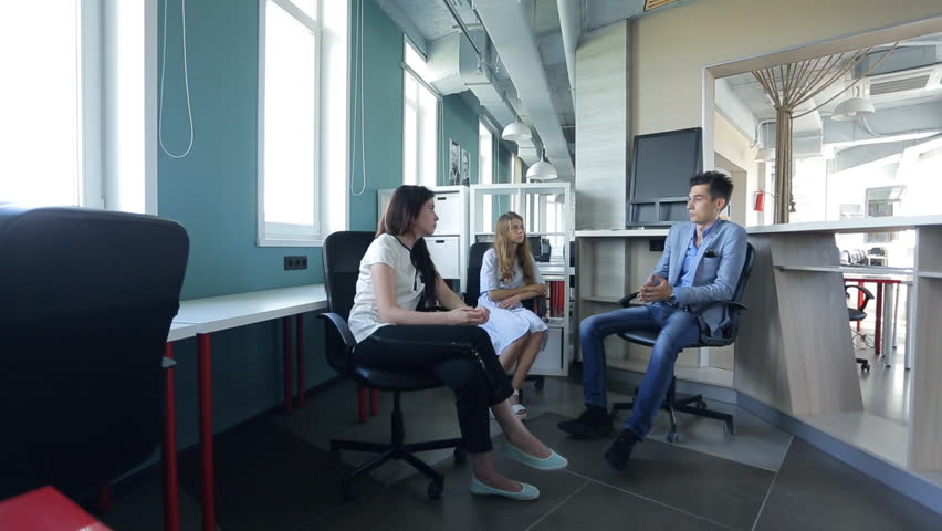 Tenant co-working office is discussing a deal with two women employees, sitting talking about possibilities. | Shutterstock HD Video #18594845