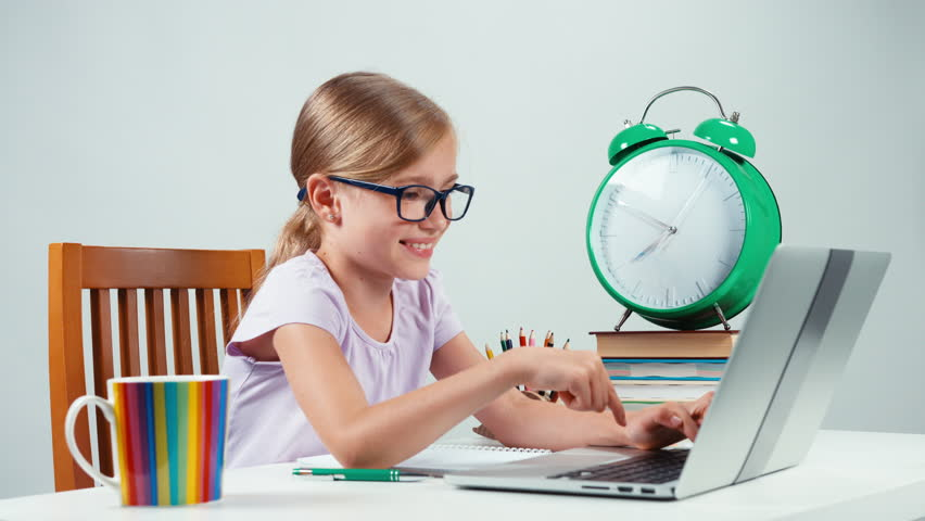 Portrait student girl 7-8 years using laptop and rejoicing. Hands up | Shutterstock HD Video #18600203
