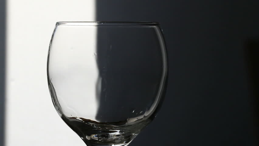 pouring water into glass, black background