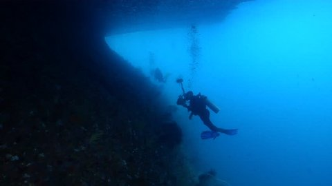 Distant group of scuba divers swimming in overhang in Indonesia, HD, UP23819
