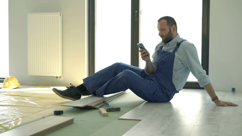 Male worker using smartphone during break from work at new home  #18638831