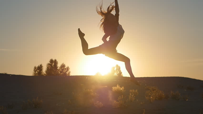 Silhouette of a girl professional dancer jumping at sunset in slow motion | Shutterstock HD Video #18649961