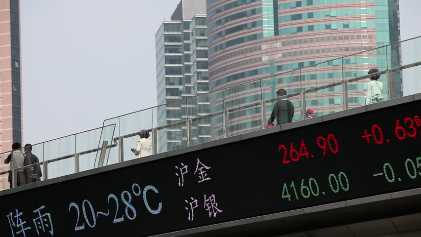 Chinese business people walk across a bridge with the Hang Seng stock market index below. (Shanghai, China 2010s)