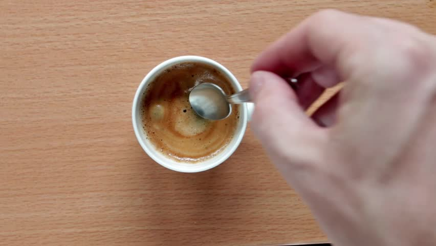 flavouring espresso with sugar and stirring it #18679811