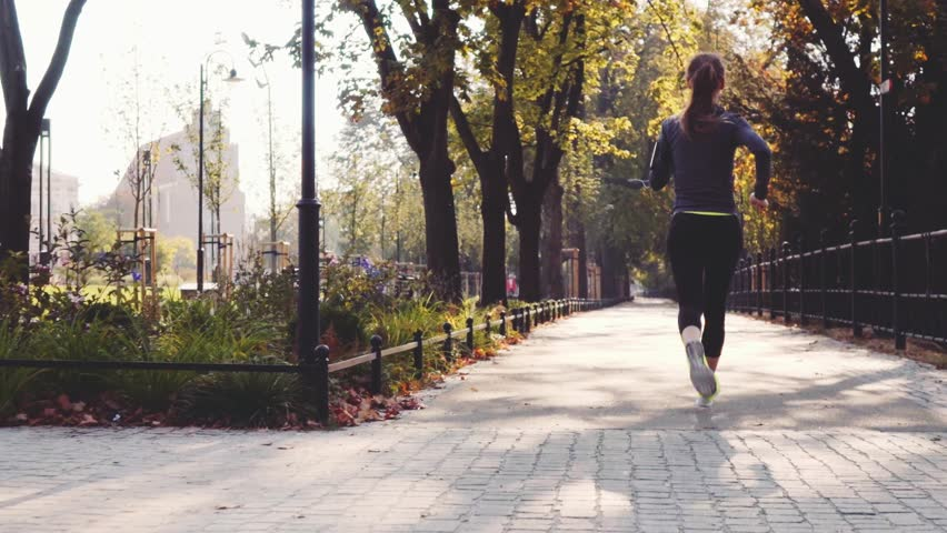 Runner Woman Running in the Sunny City Park Exercising Outdoors. Steadicam STABILIZED shot, SLOW MOTION 120 fps. Sportswoman Listening to Music during Morning Training. Healthy Lifestyle. Lens Flare. #18680996