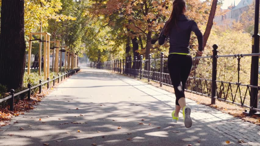 Runner Woman Running in the Sunny City Park Exercising Outdoors. Steadicam STABILIZED shot, SLOW MOTION 120 fps. Sportswoman Listening to Music during Morning Training. Healthy Lifestyle. Lens Flare. #18681002