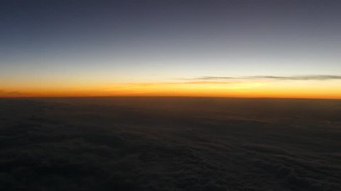 Flying above the clouds from Germany to Slovenia in a passengers plane while looking at the sunset