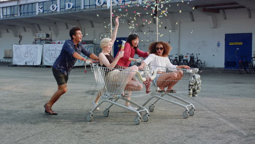 Young friends racing grocery carts. Multiracial group of young people enjoying outdoors with shopping trolley race.  #18685001