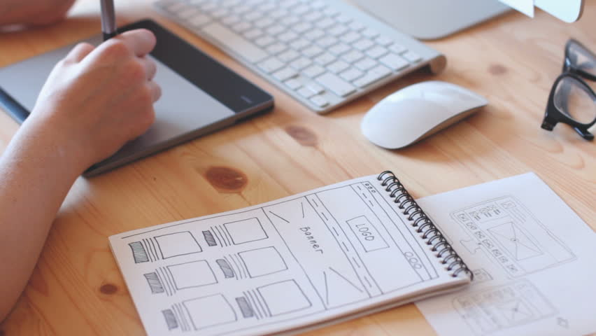 A web designer works on the graphics tablet, the site layout drawn with sketch book. | Shutterstock HD Video #18730976