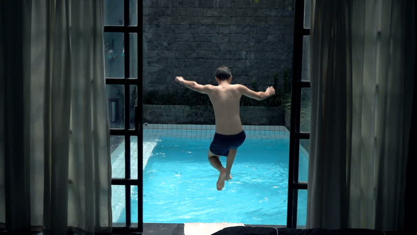 Teenage boy jumping into swimming pool, super slow motion 240fps  | Shutterstock HD Video #18756575