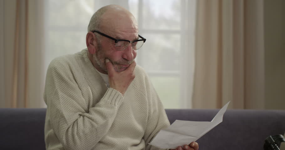 Elderly man reading the sad news of the letter and painful sigh. He has his hand on his  chest.