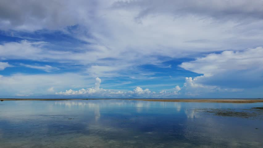 A low tide, early morning clip from the white sand beaches of San Juan, Siquijor. Shot from the water, the footage shows crystal clear ripples and sandbars.   #18764339