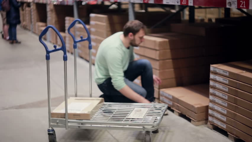 A man is taking a box from the shelf, putting it on the trolley, checking his list in a storage warehouse   Shutterstock HD Video #18772571