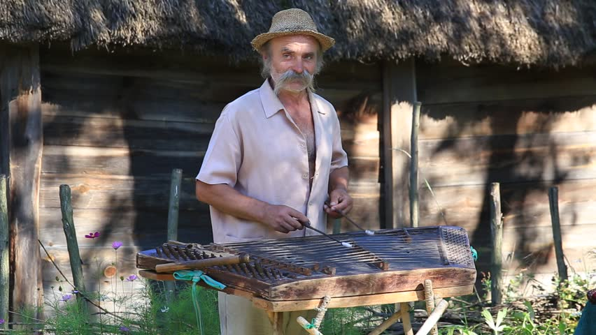 KIEV, UKRAINE - AUGUST 6, 2016 :Unknown old Ukrainian musician playing the national stringed musical instrument gusli in ethnic village Pirogovo, Kiev, Ukraine   Shutterstock HD Video #18772814