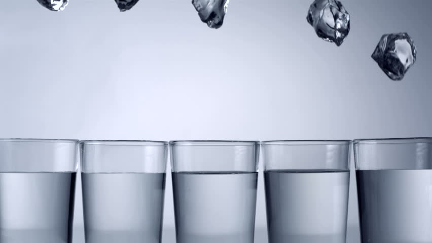 Slo-motion ice cubes falling into row of glasses