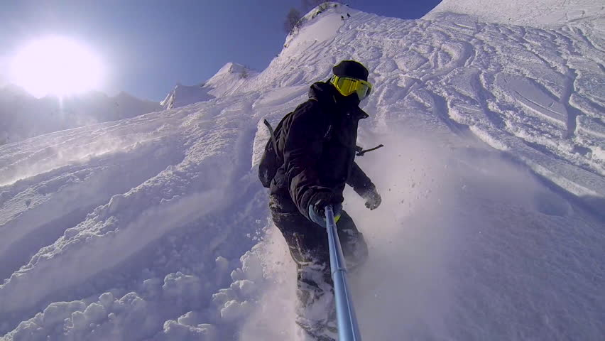 Man riding on snowboard with selfie gopro stick in his hand | Shutterstock HD Video #18781634