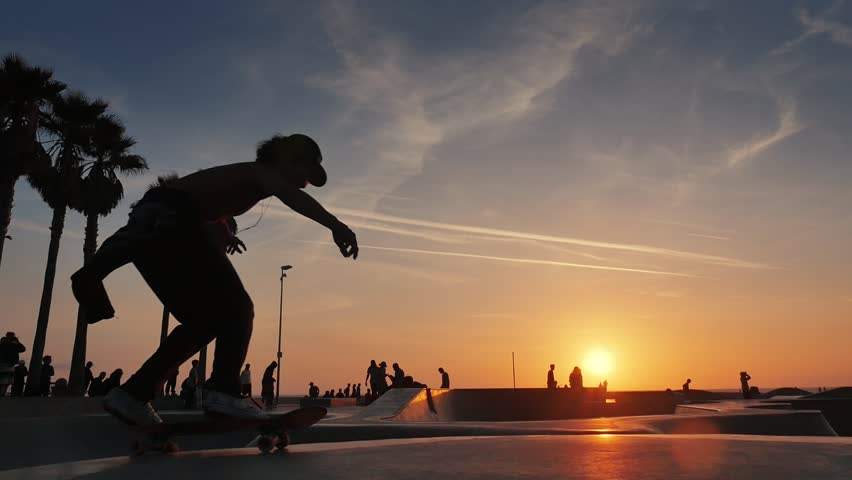 Silhouette of skater on skateboard jumping over sunset sky at Venice Beach skate park, California. Slow motion.  #18784226