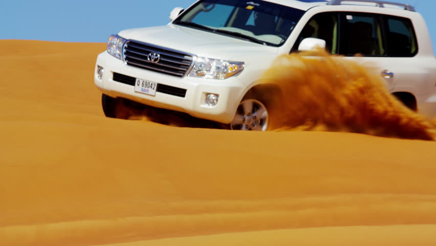 Dubai - May 2016: Aerial Drone 4x4 vehicle tourist trip taking people on exciting tours across sand dunes Dubai desert shot on RED DRAGON