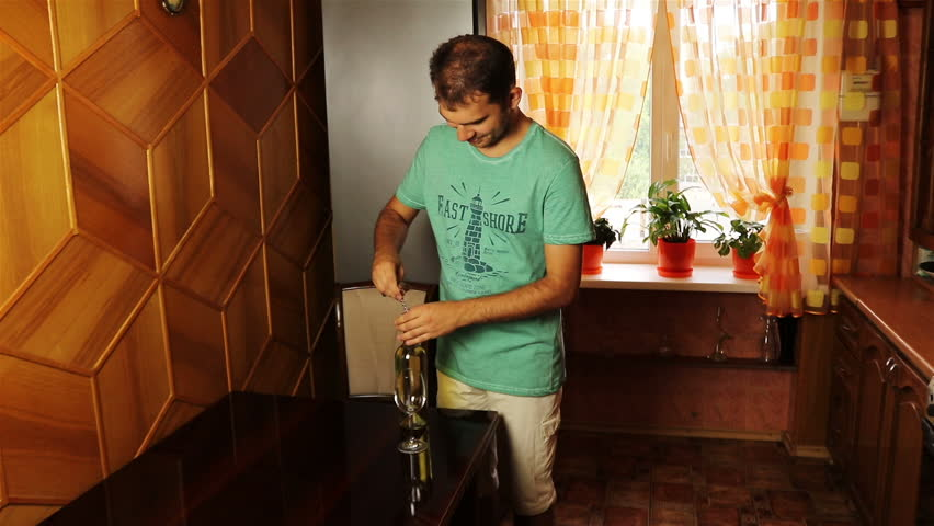 Handsome young man opening the white wine and pouring it to the glass | Shutterstock HD Video #18825944