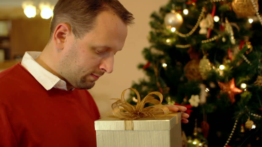 Amazed man looking at magical gift in the box, christmas tree in background | Shutterstock HD Video #1883647